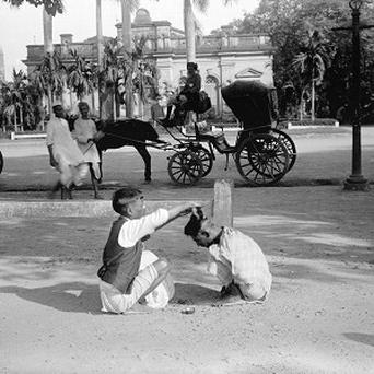 A street hairdresser giving a 'Hindustani haircut' (pudding bowl) on Strand Road South, Kolkata (RCAHMS/PA)