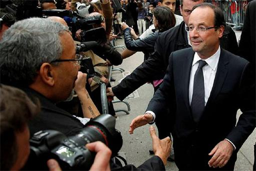 France's newly-elected President Francois Hollande reaches out to shake hands as he leaves his campaign headquarters in Paris. Photo: Reuters