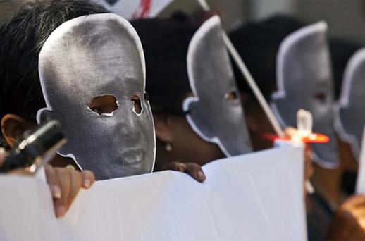 Thai activists wearing masks showing imprisoned Ampon Tangnoppakul during a protest held outside the criminal court in Bangkok. Photo: Getty Images