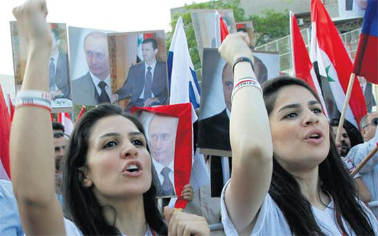 Supporters of Syrian President Bashar al-Assad attend a celebration, organised for Russian President Vladimir Putin after he was sworn in as president yesterday, in front of the Russian embassy in Damascus.