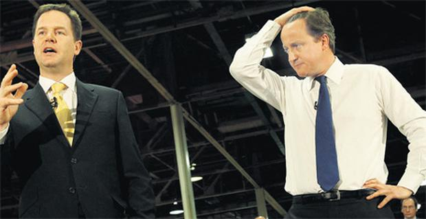 Britain's Prime Minister David Cameron listens to Deputy Prime Minister Nick Clegg, left, during a meeting at CNH Tractors in Basildon, southeast England, yesterday
