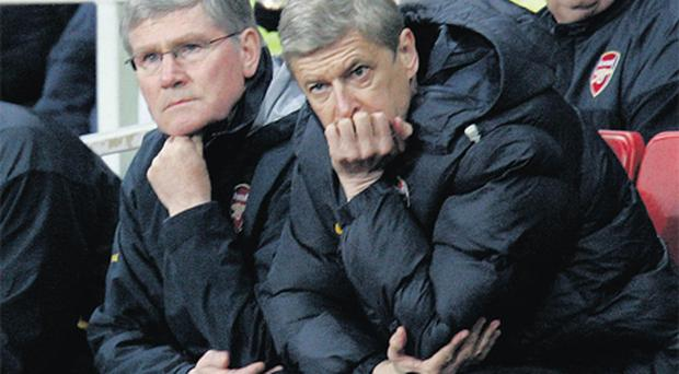 Pat Rice and Arsene Wenger strike a familiar pose in the dugout at the Emirates Stadium