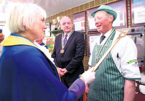 Annie Beresford places a large fork on the shoulder of Donegal town butcher Diarmuid McGettigan as he is made a knight of the Order of Commanderie des Fins Goustiers du Duche d'Alencon, France