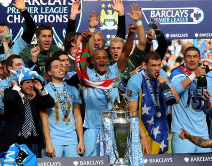 MANCHESTER, ENGLAND - MAY 13: The Manchester City players celebrate with the trophy following the Barclays Premier League match between Manchester City and Queens Park Rangers at the Etihad Stadium on May 13, 2012 in Manchester, England. (Photo by Alex Livesey/Getty Images)