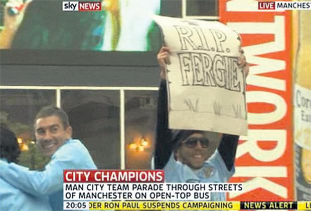 A picture grab shows Carlos Tevez adding an unsavoury chapter to the simmering rivalry between Manchester City and Manchester United by holding a banner proclaiming 'RIP Fergie' during his club's Premier League title trophy parade through the city last night