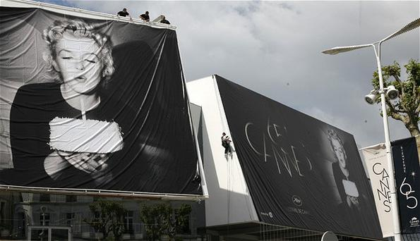 Workers set up giants 65th Cannes Film Festival official posters showing Marilyn Monroe on the Cannes Festival Palace. Photo: AP