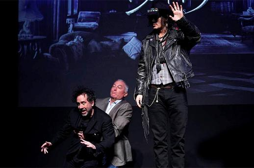 A member of staff catches director Tim Burton (L) as he falls off a stage while actor Johnny Depp (R) waves during a photo call at a news conference for their film 'Dark Shadows' in Tokyo. Photo: Reuters
