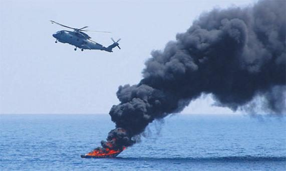 A Merlin 502 helicopter (top left) from the British Royal Navy's 'HMS Westminster' fires at a Somali pirate vessel which bursts into flames on impact.