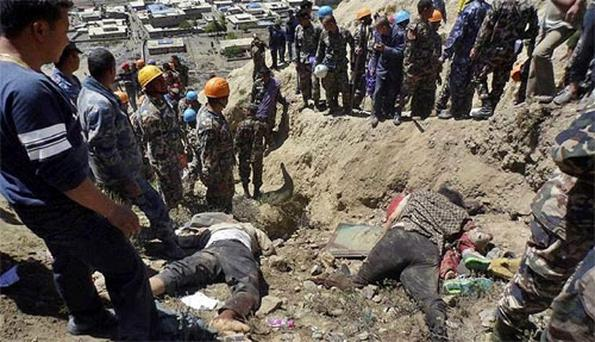 Bodies of victims of plane crash lie on the ground as Nepalese rescue workers inspect the site of the crash near Jomsom, Nepal. Photo: Associated Press