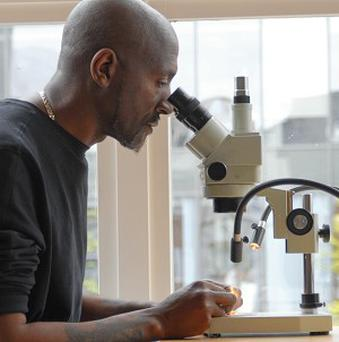 Willard Wigan works on what is believed to be the world's smallest-ever portrait of the Queen, on a coffee bean