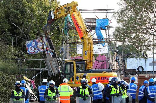 A mechanical vehicle begins to demolish the scaffolding tower at the main entrance to the Dale Farm travellers site. Photo: PA