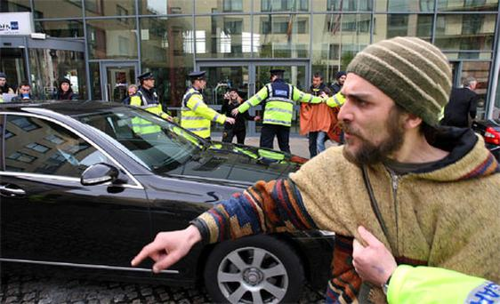 Gardai restrain protesters as Taoiseach Enda Kenny is driven away after he spoke on the fiscal treaty referendum at a breakfast briefing hosted by Galway Chamber and IBEC at the Radisson Blu Hotel in Galway.