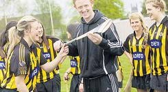 Kerry footballer Colm 'Gooch' Cooper gets a hurling lesson from Grace Walsh, sister of Kilkenny hurling star Tommy, during a visit to the Loreto Convent in Kilkenny yesterday as part of the AIB Build a Bank Competition
