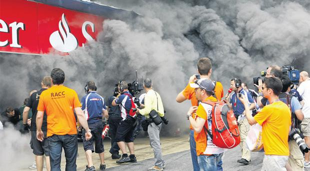 Smoke pours from the Williams's team garage destroyed by the fire at the end of the Spanish Grand Prix