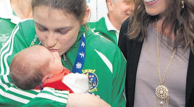 Katie kisses her niece Madeleine while sister Sarah looks on