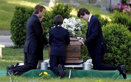 Robert F. Kennedy Jr., left, kneels with his children at the casket of Mary Richardson Kennedy, in St. Francis Xavier Cemetery in Centerville, Mass. Photo: AP
