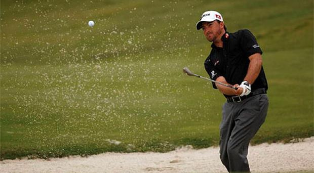 Graeme McDowell of Britain hits out of a bunker during his match against Rafael Cabrera-Bello of Spain on the 10th hole during the World Match Play Championship semi-finals in Casares, near Malaga, southern Spain. Photo: Reuters
