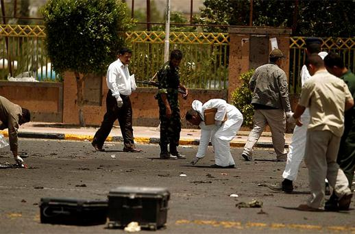 Forensic policemen collect evidence at the site of a suicide bomb attack at a parade square in Sanaa. Photo: Reuters