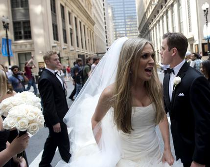 A bride and groom walk past as Chicago Occupy Wall Street Protesters march through the streets of downtown Chicago, Illinois, May 19, 2012