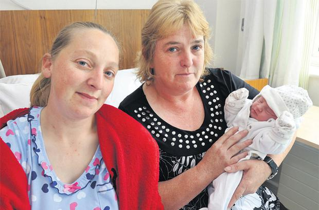 Claire O'Driscoll holds her new grandchild Siobhan after acting as midwife when her daughter Sinead O'Donoghue (left) gave birth on the way to hospital yesterday