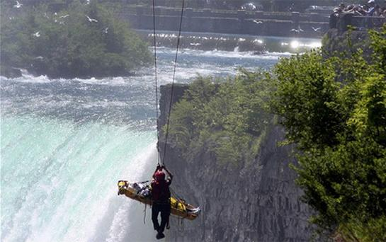 Niagara Falls firefighter Matt Rozon and an unidentified man are lifted from the Niagara gorge by an aerial fire truck in Niagara Falls. Photo: Reuters