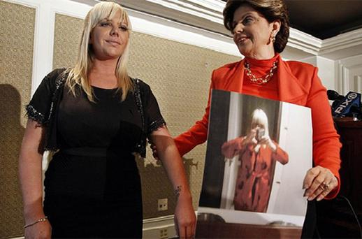 Lauren Odes and her attorney Gloria Allred speak at a news conference in New York. Ms Odes says she was forced to wear a baggy bathrobe, as seen in the picture held up by Gloria Allred. Photo: Reuters