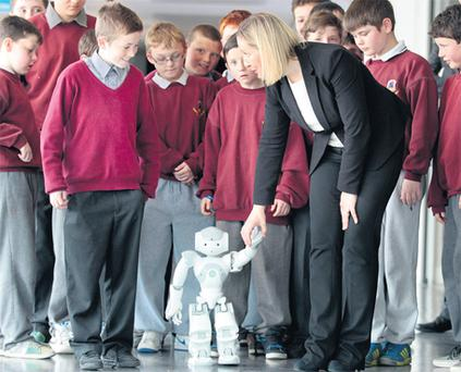 Junior minister Lucinda Creighton with Nao the robot and children from Fionnbarra Naofa National School, one of Intel's e-schools, at the launch of the exhibit at Trinity College, Dublin, yesterday