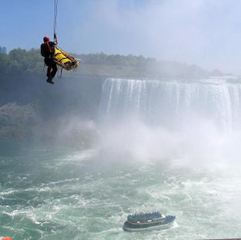 Emergency officials rescue a man who plunged over Niagara Falls and survived in an apparent suicide attempt (AP/Harry Rossetani)