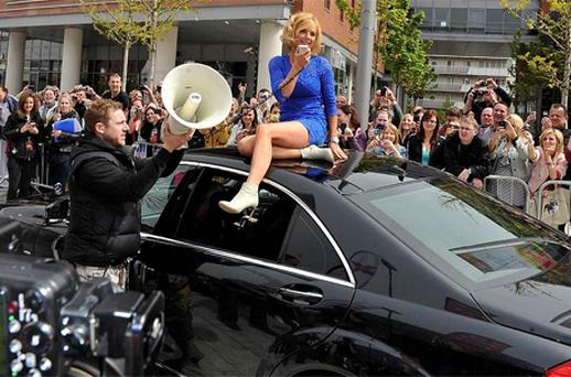 Geri Halliwell sits on top of a car after she arrives for the first round of X Factor auditions at the Echo Arena, Liverpool. Photo: PA