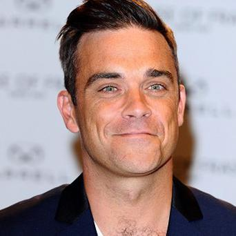 Robbie Williams is looking forward to playing football with his child