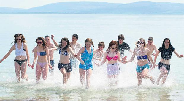 Pupils from Athenry in Co Galway on the beach in Salthill yesterday, taking a dip and enjoying the fine weather