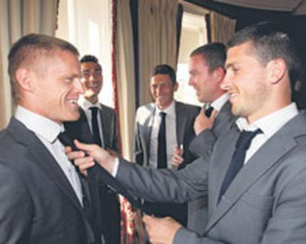 Shane Long fixes Damien Duff's tie while they try on the squad's Euro 2012 suit, along with Stephen Kelly, Keith Andrews and Richard Dunne