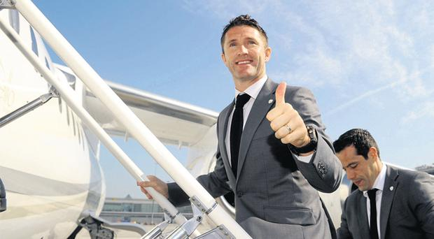 Republic of Ireland captain Robbie Keane boards a plane as the squad departed for Italy yesterday on the first leg of their Euro 2012 odyssey