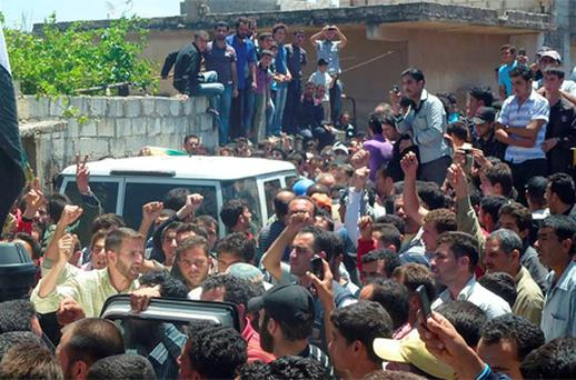 Residents shout as they gather around a vehicle carrying United Nations observers in Houla, near Homs