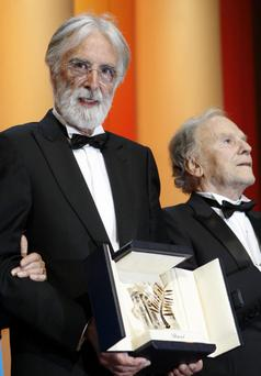 Director Michael Haneke, left, is presented the Palme d'Or award for Love during the awards ceremony at the 65th international film festival, in Cannes, southern France, Sunday, May 27, 2012. At right is actor Jean-Louis Trintignant. (AP Photo/Lionel Cironneau)