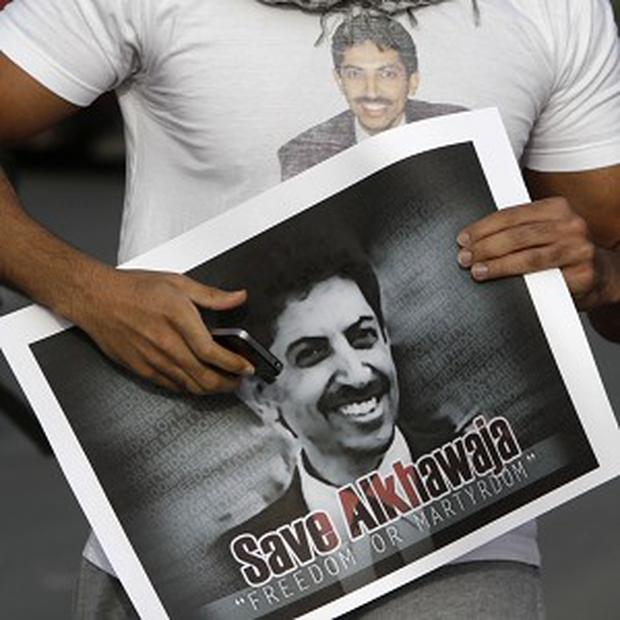 A Bahraini anti-government demonstratorcarries a placard with pictures of Abdulhadi al-Khawaja, who has been on hunger strike for 110 days (AP)