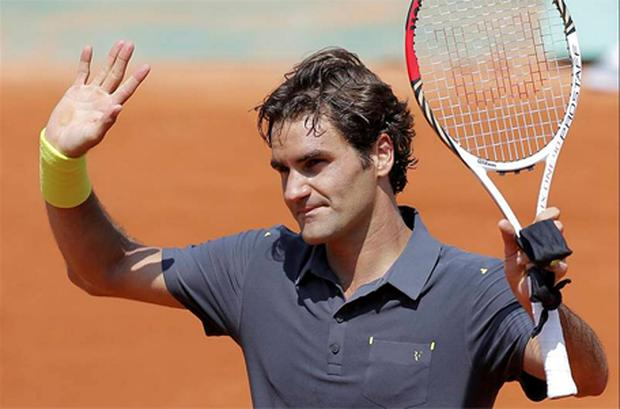 Roger Federer waves after defeating Germany's Tobias Kanke during their first round match in the French Open