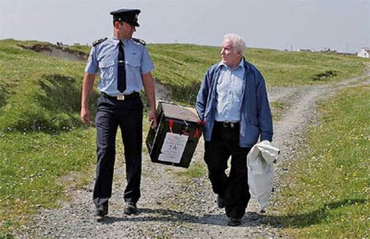Garda John O'Toole (left) and Hugh O' Donnell Presiding Officer leave the polling station with the ballot box after voting on the fiscal treaty referendum on Inishfree Island off the coast of Donegal, Ireland.