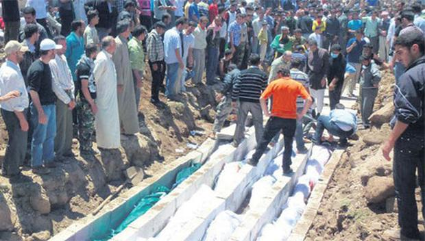 Mourners gather at a mass burial for the victims of an artillery barrage from Syrian forces in Houla.