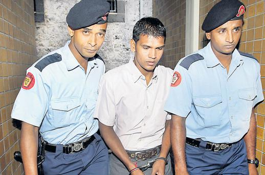 Avinash Treebhoowoon is led from court in Port Louis, Mauritius, yesterday during the Michaela McAreavey murder trial. Photo: STEVE HUMPHREYS