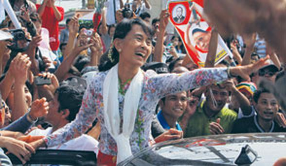 Pro-democracy leader Aung San Suu Kyi is greeted by migrant workers from her home country on a visit to Thailand yesterday