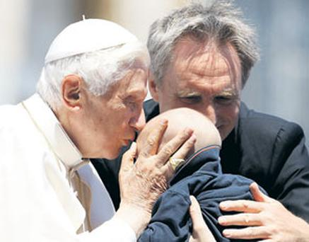 Pope Benedict XVI kisses a baby while leading the weekly audience in St Peter's Square at the Vatican yesterday. Photo: REUTERS/ALESSANDRO BIANCHI