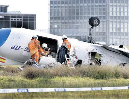 Fire officers examine the scene of the fatal crash at Cork Airport in February 2011