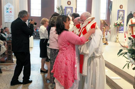 Deacon Eric Cooney receives his vestments from his wife Denise at yesterday's ceremony