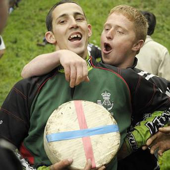 Chris Anderson (left) celebrates after winning the first race during the annual Cheese Rolling competition in Gloucestershire