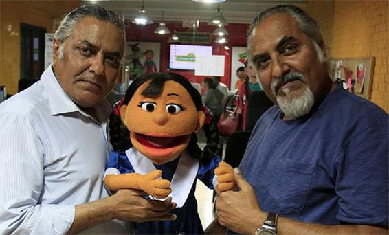 Faizaan Peerzada, left, chief operating officer of the Rafi Peer Theater Workshop, and Sadaan Peerzada, right, pose with a character, Rani, from the Pakistani version of Sesame Street on Tuesday, June 5, 2012 in Lahore, Pakistan. Photo: Associated Press