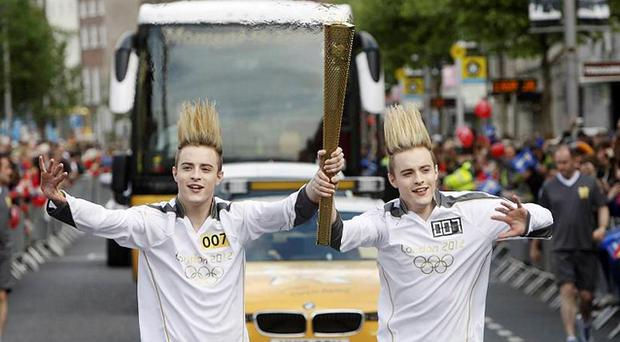Jedward carrying the Olympic Flame on the Torch Relay leg through Dublin. Photo: PA