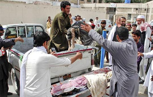 Pakistani man carries the lifeless body of a child who was killed in a bomb explosion to a hospital in Quetta, Pakistan. Photo: Associated Press