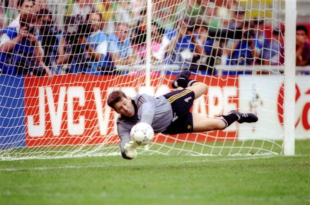 Bonner dives and saves in the penalty shoot-out against Romania at Italia 90. Dave O'Leary went on to net the winner.