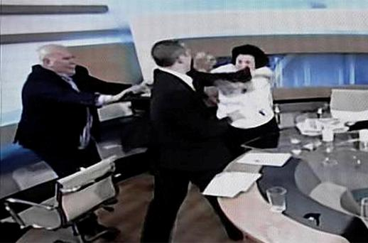 Ilias Kasidiaris (2nd L), the spokesman for Greece's far-right party Golden Dawn, slaps Communist Party deputy Liana Kanelli on live television
